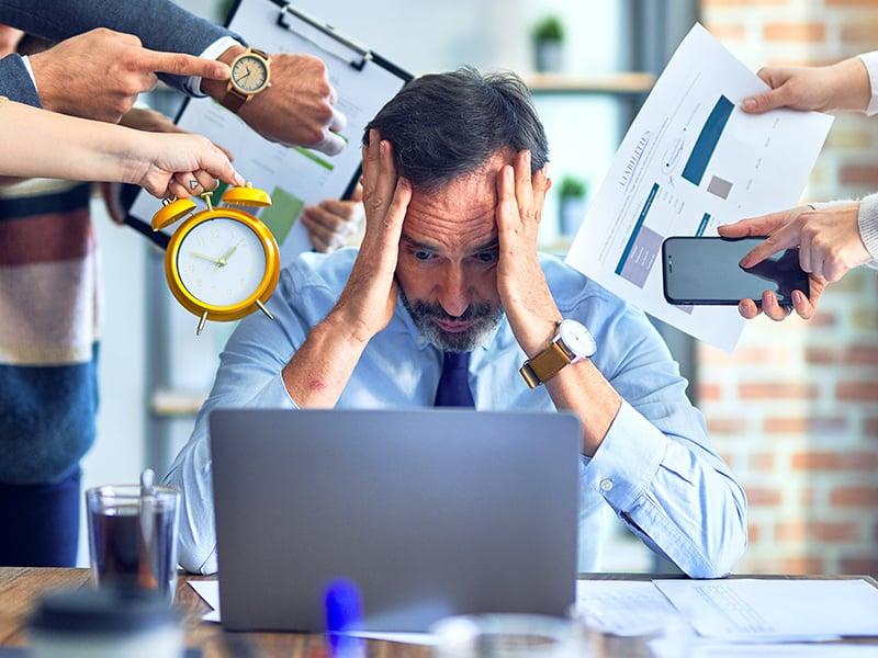 Echelon Health - work stress blog - man sat at desk being hassled - corporate health assessment