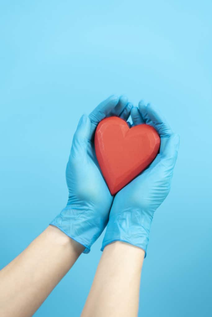 Female hands wearing blue medical gloves holding red heart over light blue background. Health care, heart disease, cardiology